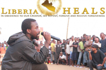 SPREADING THE GOSPEL OF HEALING: Putugah Takpaw Phenom, a 27 year old Liberian hip hop musician, using his voice to promote a message about repentance and forgiveness to a crowd at a Liberia Heals roadside event
